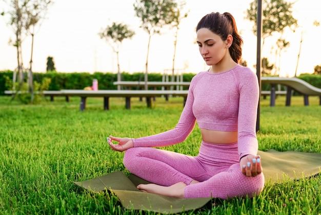 Jovem de camisa rosa e calças, sentado na grama dentro do parque, meditando e fazendo yoga