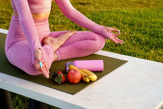 Jovem de camisa roxa e calças na grama durante o dia dentro do parque verde, meditando a garrafa de ioga