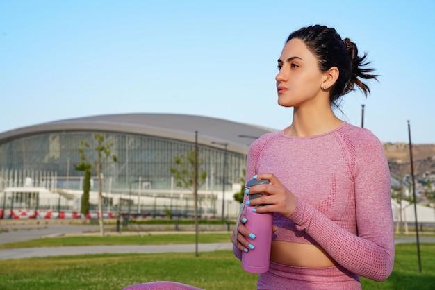 Jovem de camisa roxa e calças na grama durante o dia dentro do parque verde segurando a garrafa rosa
