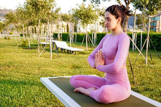 Jovem de camisa roxa e calças na grama durante o dia no parque verde, meditando e fazendo yoga em poses diferentes