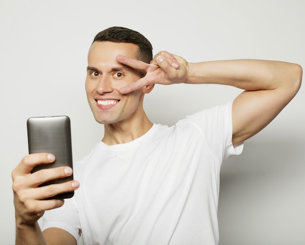 Jovem de camisa, segurando o telefone móvel e fazer foto dele