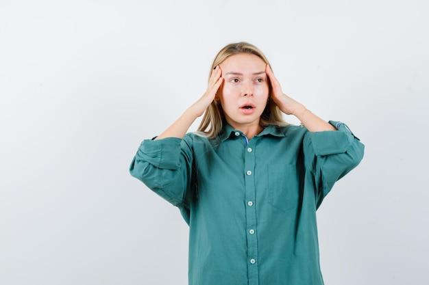 Jovem de camisa verde de mãos dadas nas têmporas e parecendo indefesa