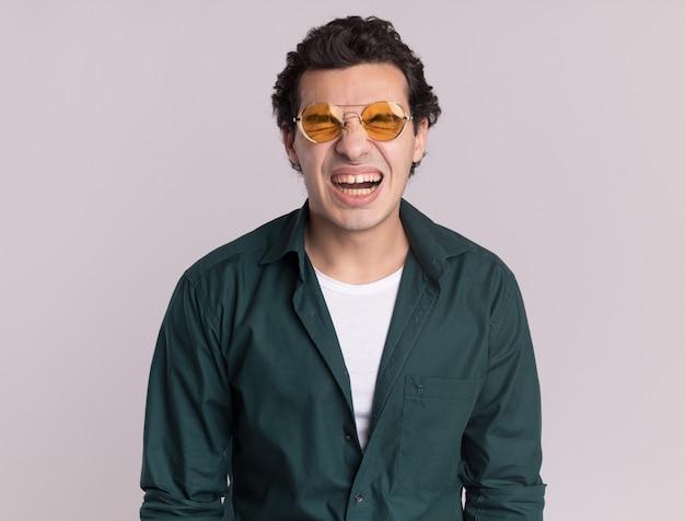 Jovem de camisa verde de óculos irritado e irritado gritando com os olhos fechados em pé sobre uma parede branca