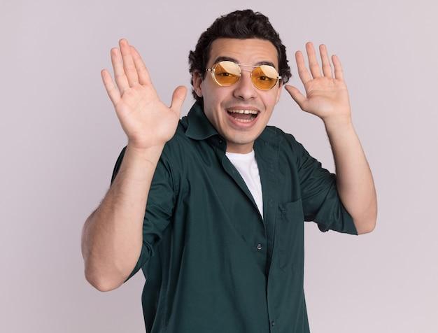 Jovem de camisa verde de óculos, olhando para a frente, feliz e surpreso, levantando os braços em pé sobre uma parede branca