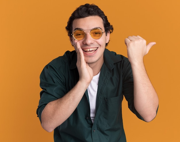 Jovem de camisa verde de óculos, olhando para a frente, sorrindo alegremente com a mão perto da boca apontando com o polegar para o lado em pé sobre a parede laranja