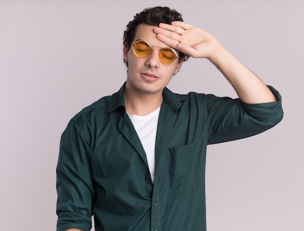 Jovem de camisa verde de óculos, parecendo cansado e entediado, com a mão na testa em pé sobre uma parede branca
