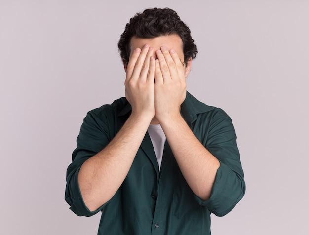 Jovem de camisa verde fechando os olhos com a mão em pé sobre uma parede branca