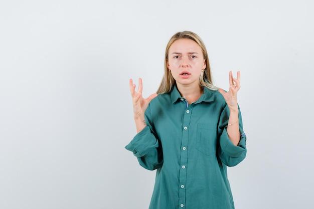 Jovem de camisa verde levantando as mãos e parecendo agitada