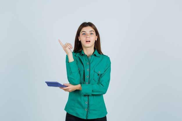 Jovem de camisa verde segurando calculadora enquanto mostra o gesto de eureka, apontando para cima e parecendo surpresa, vista frontal.