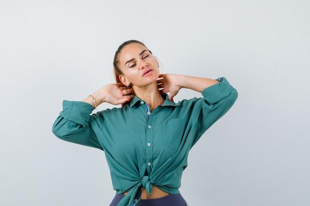 Jovem de camisa verde, sofrendo de dor no pescoço e parecendo cansada, vista frontal.