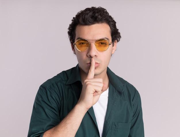 Jovem de camisa verde usando óculos, olhando para a frente com uma cara séria com dedo nos lábios gesto de silêncio em pé sobre uma parede branca