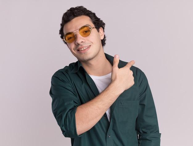 Jovem de camisa verde usando óculos, olhando para a frente, sorrindo, apontando com o dedo para trás em pé sobre uma parede branca