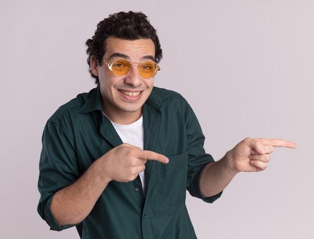 Jovem de camisa verde, usando óculos, olhando para a frente, sorrindo maliciosamente, apontando com o dedo indicador para o lado em pé sobre uma parede branca
