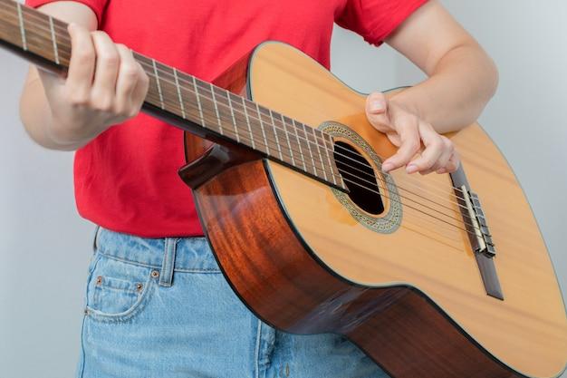 Jovem de camisa vermelha segurando uma guitarra de madeira