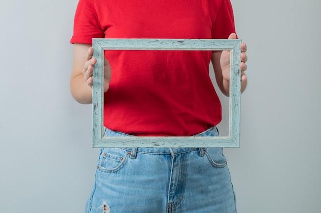 Jovem de camisa vermelha segurando uma moldura de foto metálica