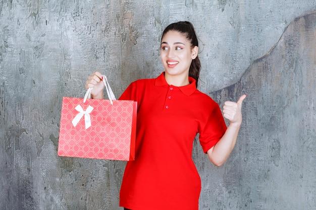 Jovem de camisa vermelha, segurando uma sacola de compras vermelha e mostrando sinal positivo com a mão.