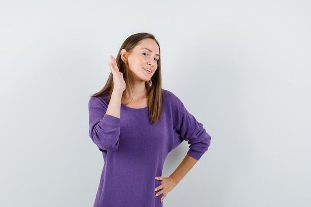 Jovem de camisa violeta, segurando a mão atrás da orelha e olhando curiosa, vista frontal.