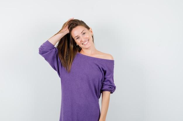 Jovem de camisa violeta, segurando a mão no cabelo e olhando alegre, vista frontal.
