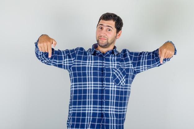 Jovem de camisa xadrez apontando os dedos para baixo e parecendo positivo