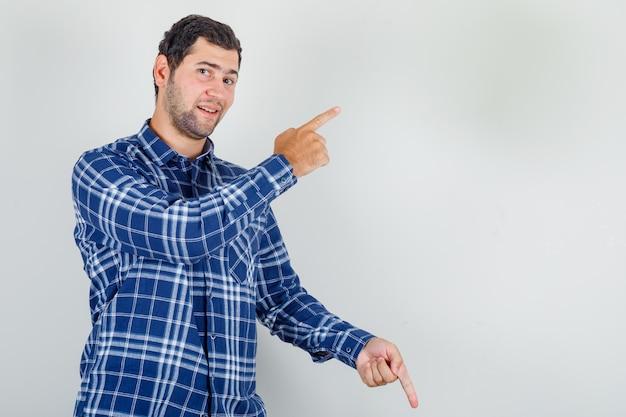 Jovem de camisa xadrez apontando os dedos para cima e para baixo e parecendo feliz