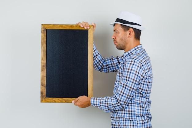 Jovem de camisa xadrez, chapéu segurando uma lousa e olhando focado