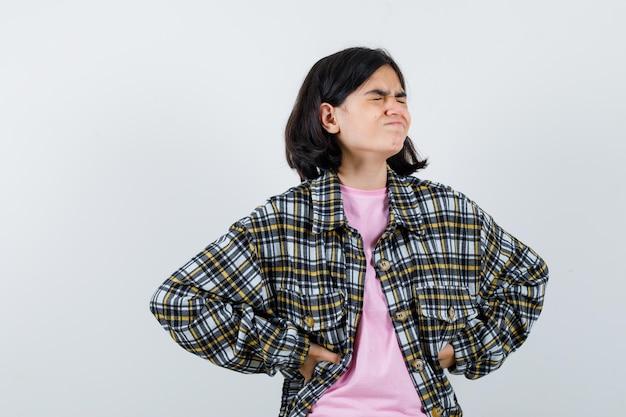 Jovem de camisa xadrez e camiseta rosa de mãos dadas na cintura, fechando os olhos e fazendo careta e parecendo cansada, vista frontal.