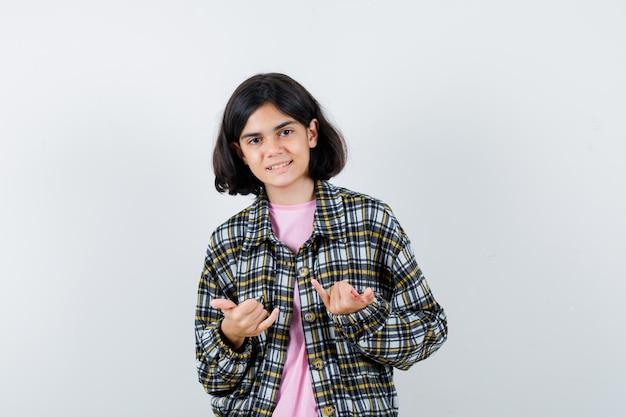 Jovem de camisa xadrez e camiseta rosa, mostrando o dedo mindinho e o gesto de rock n roll e olhando fofa, vista frontal.