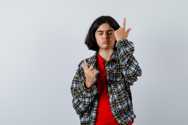 Jovem de camisa xadrez e camiseta vermelha apontando para cima com o dedo indicador, fechando os olhos e olhando séria, vista frontal.