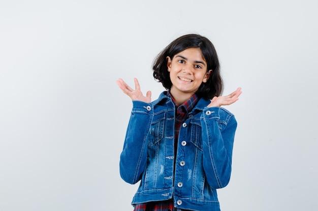 Jovem de camisa xadrez e jaqueta jeans, esticando as mãos de forma questionadora e bonita, vista frontal.