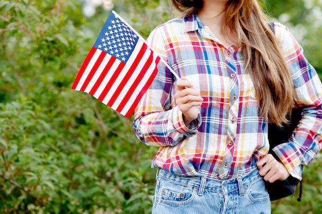 Jovem de camisa xadrez e shorts segurando a bandeira americana