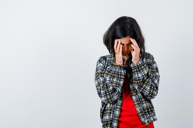 Jovem de camisa xadrez e t-shirt vermelha com dor de cabeça e parecendo apressada, vista frontal.