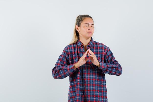 Jovem de camisa xadrez mostrando gesto de seguro enquanto fecha os olhos e parece séria