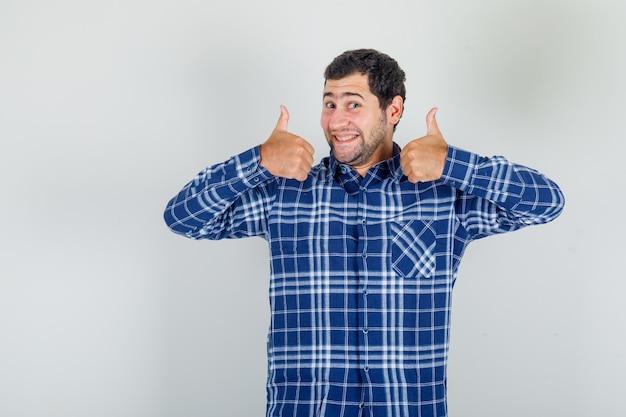 Jovem de camisa xadrez mostrando os polegares para cima e parecendo satisfeito