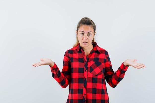 Jovem de camisa xadrez mostrando um gesto desamparado e parecendo confusa