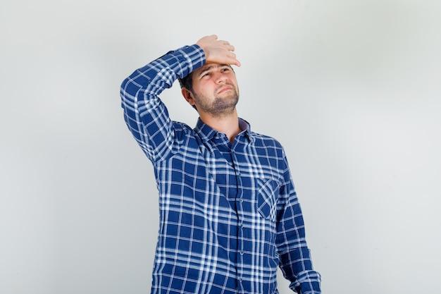 Jovem de camisa xadrez sofrendo de dor de cabeça com a mão na testa