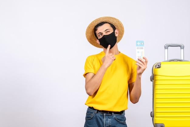 Jovem de camiseta amarela em pé perto da mala amarela segurando uma passagem de viagem piscando os olhos