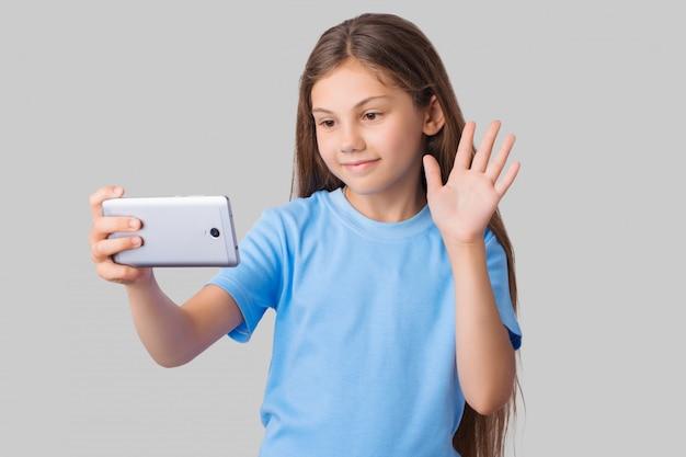 Jovem de camiseta azul, acenando para o telefone móvel, enquanto ela está usando chamadas de vídeo. pequena estudante com cabelo comprido isolado