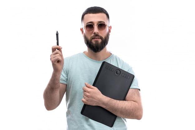 Jovem de camiseta azul com barba e óculos escuros, segurando arquivos de caneta