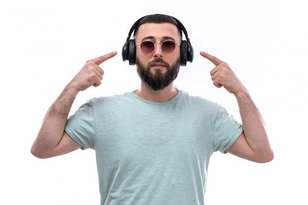 Jovem de camiseta azul com barba ouvindo música através de fones de ouvido pretos