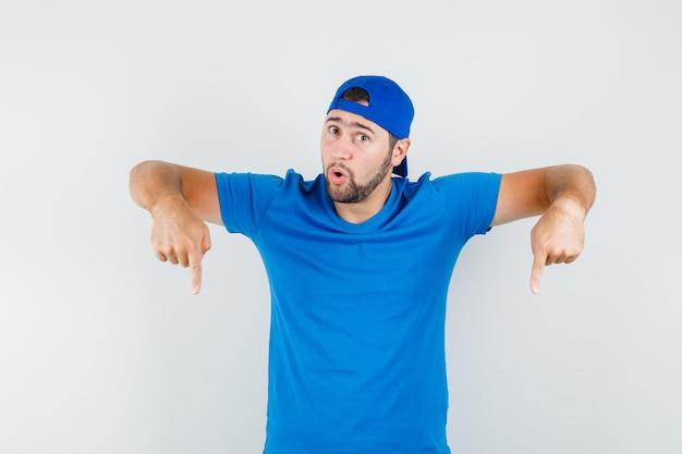 Jovem de camiseta azul e boné apontando para baixo e parecendo maravilhado