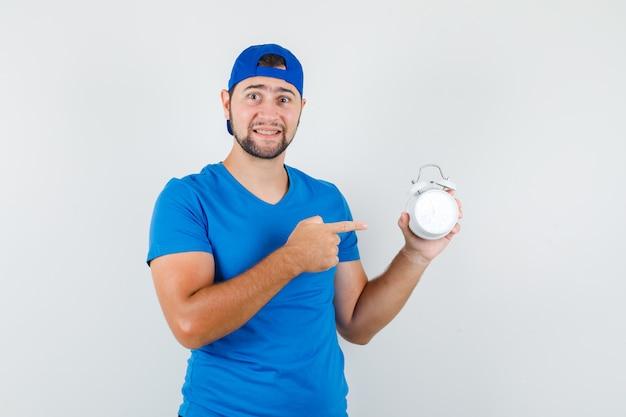 Jovem de camiseta azul e boné apontando para o despertador e parecendo positivo