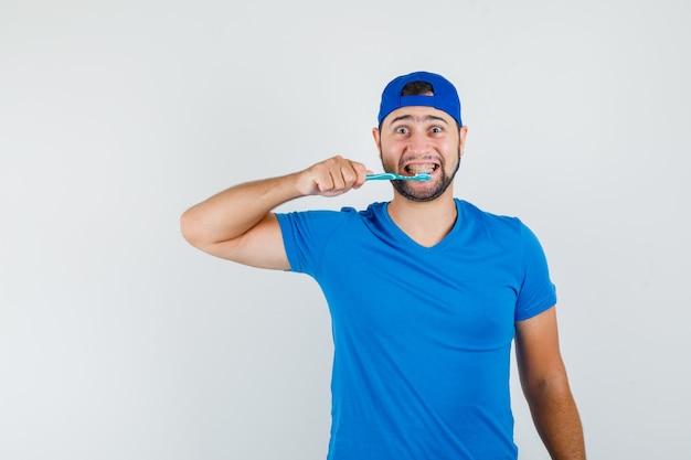 Jovem de camiseta azul e boné, escovando os dentes e parecendo positivo