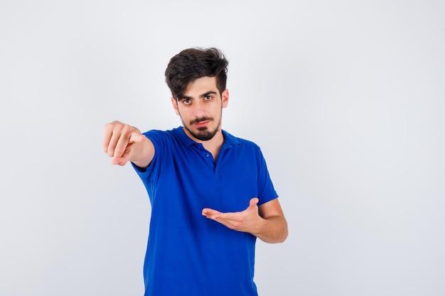 Jovem de camiseta azul esticando uma das mãos, segurando algo e apontando para a frente, parecendo sério