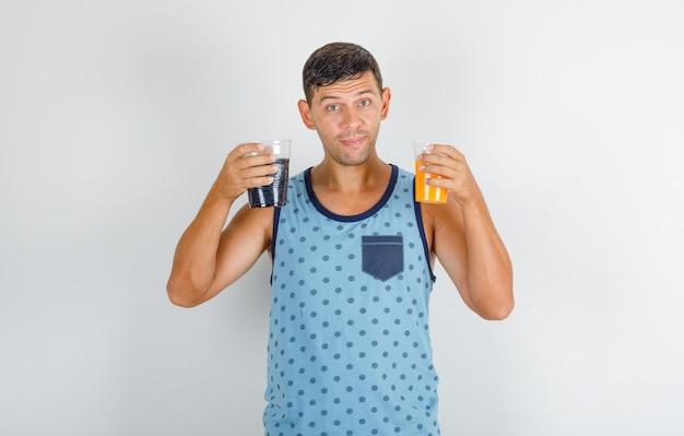 Jovem de camiseta azul segurando refrigerantes