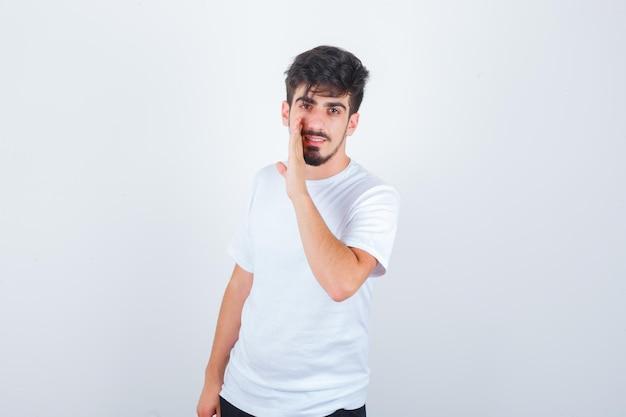 Jovem de camiseta branca contando um segredo por trás das mãos e parecendo confiante