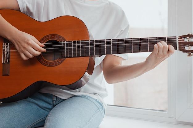 Jovem de camiseta branca e calça jeans azul está sentada no parapeito da janela e tocando violão. perto das mãos. a menina pega um acorde apertando as trastes no braço da guitarra