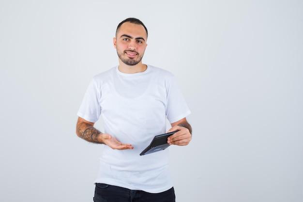 Jovem de camiseta branca e calça preta segurando uma calculadora, apontando para ela e parecendo feliz