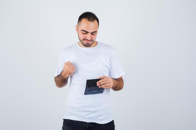 Jovem de camiseta branca e calça preta segurando uma calculadora e cerrando os punhos e parecendo sério