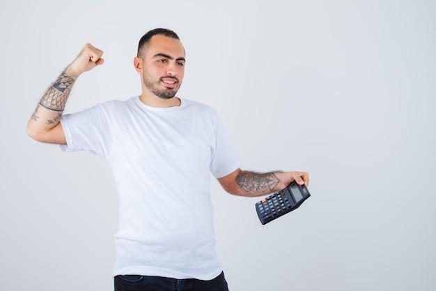 Jovem de camiseta branca e calça preta segurando uma calculadora e mostrando o gesto do vencedor e parecendo feliz