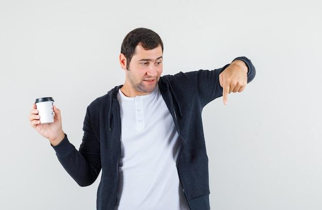 Jovem de camiseta branca e capuz preto com zíper na frente segurando a xícara de café para viagem e apontando para baixo com o dedo indicador e parecendo surpreso, vista frontal.